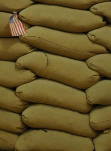 An american flag placed into a sandbag filled wind